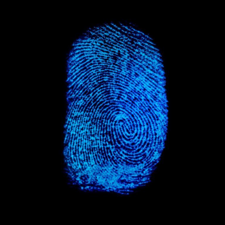 Blue fingerprint identification symbol isolated on black background in technology concept