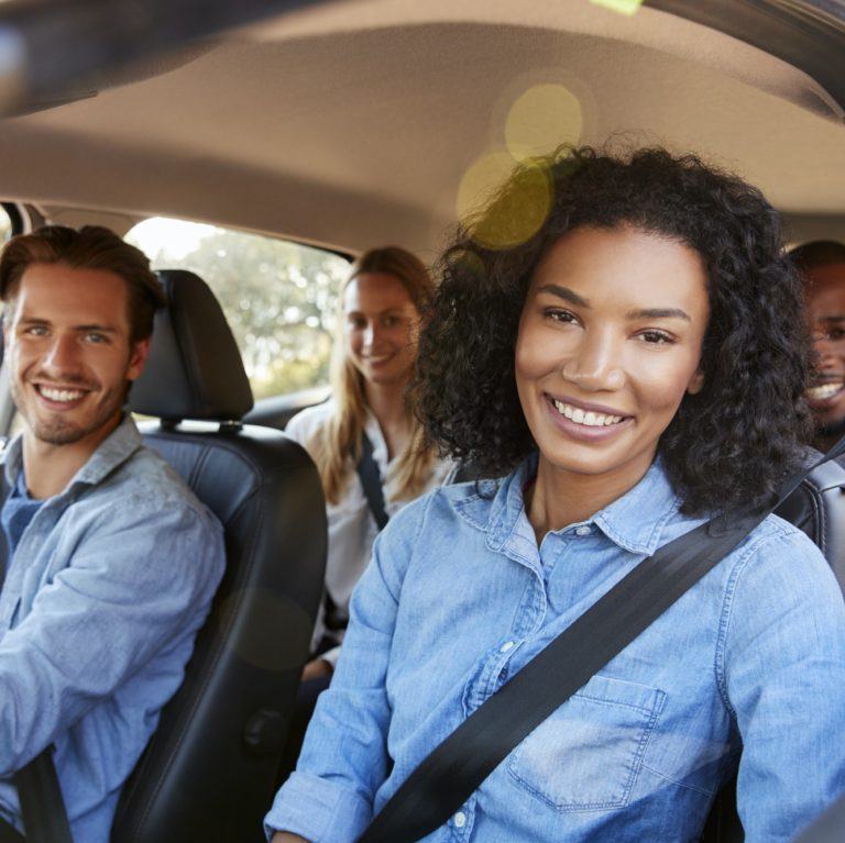Four adult friends in a car on a road trip smiling to camera