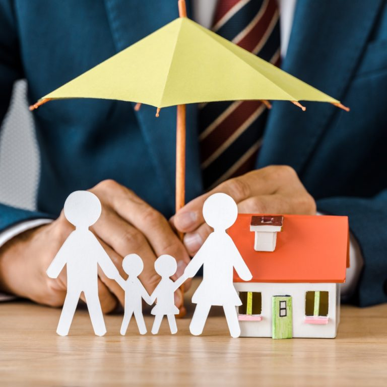 Male hands with paper cut family, house model and umbrella on wooden table, life insurance