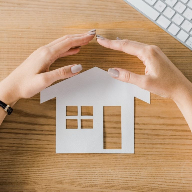 Partial view of businesswoman covering house paper model on wooden tabletop with hands, insurance