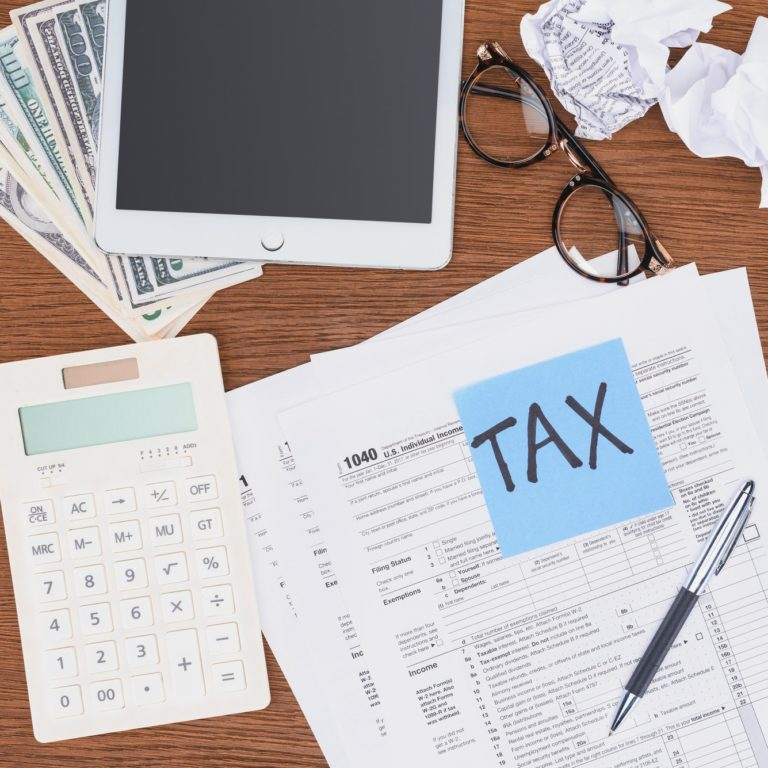 top view of tax forms, digital devices and blue card with 'tax' word on desk